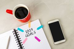 2019 goals text on note pad. With smart phone and pen royalty free stock images