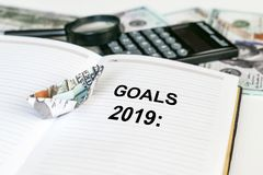 2019 goals text in open notebook with dollar banknote origami ship and calculator, money and magnifier in the background. Business financial Concept stock photo