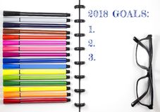 2018 Goals text on white sketchbook with color pen and eye glasses, Top View/Flat Lay. White isolated Stock Photos