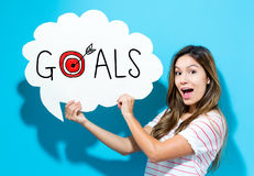 Goals text with young woman holding a speech bubble. On a blue background Stock Image