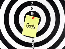 Goals word on yellow note with red pushpin on target center of dartboard. Goals word on yellow note, aim and achievement concept Royalty Free Stock Image