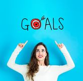 Goals with young woman looking upwards. Goals with young woman reaching and looking upwards Stock Image