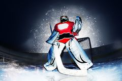 Goaltender at hockey arena in searchlight rays. Low angle view of young goaltender standing at ice hockey arena in the rays of searchlight royalty free stock image