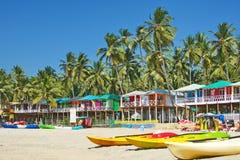 Goastrand Palolem India, kleurrijke bungalowwen onder de palm Stock Foto