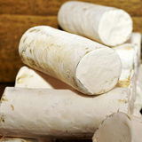 Goat cheese. Some rolls of artisan goat cheese in a market stall Stock Image