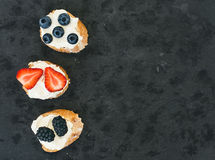 Goat cheese and berries mini-sandwitches on a dark stone background stock photo