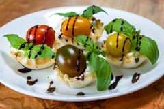 Goat cheese bites. Delicious puff pastry cups filled and baked with goat cheese topped with fresh basil and tomato with a balsamic drizzle stock photography