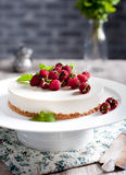 Goat cheese cheesecake with fresh raspberries. And mint leaves on top on a white plate Royalty Free Stock Photo