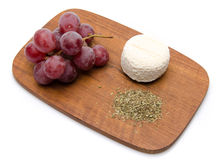Goat cheese, grapes and provencal herbs on a wooden cutting boar Royalty Free Stock Photos