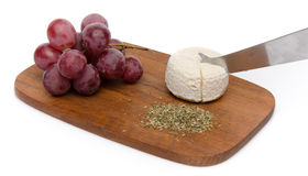 Goat cheese, grapes and provencal herbs on a wooden cutting boar Royalty Free Stock Image