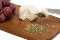 Goat cheese, grapes and provencal herbs on a wooden cutting boar Stock Photo