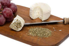 Goat cheese, grapes and provencal herbs on a wooden cutting boar Stock Images