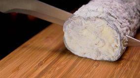 Goat cheese with gray mold is cut with a knife on a wooden board stock footage