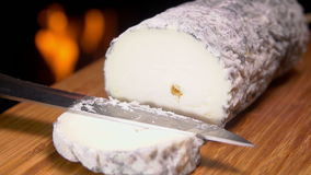 Goat cheese with gray mold is cut with a knife on a wooden board stock video