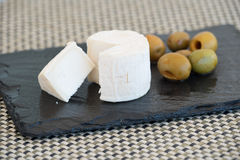 Goat cheese  and olives on a black plate. Goat cheese sliced and olives on a black plate Stock Image