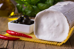 Goat cheese with olives. Fresh goat cheese with olives, chili and basil Royalty Free Stock Photos