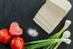 Goat cheese red ripe tomatoes and young onion with salt on black slate royalty free stock image