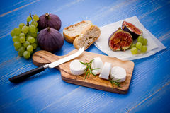Goat cheese with ripe figs and grapes Stock Image