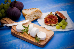 Goat cheese with ripe figs and grapes Royalty Free Stock Photos