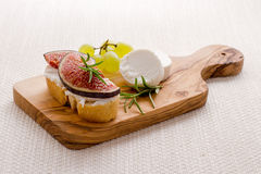 Goat cheese with ripe figs and grapes Royalty Free Stock Images