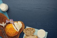 Goat cheese with saffron, bread and milk on turquoise background. View from above. Horizontal stock photo