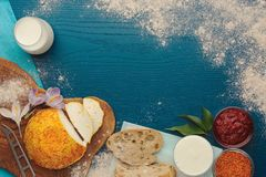 Goat cheese with saffron, bread and milk on turquoise background. View from above stock photography