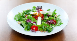 Goat Cheese Salad. A fresh salad made of mixed lattuces, cherry tomatoes, nuts, goat cheese and dijon mustard on top Royalty Free Stock Image