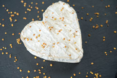 Goat cheese in the shape of a heart on a black background. Goat cheese in the shape of a heart with yellow pollen on a black background Royalty Free Stock Photos