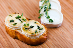 Goat cheese with thyme gratinated with honey. Stock Photo