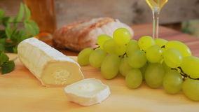 Goat cheese with white wine, grapes and bread. Circular movement of the camera around a piece of goat cheese on a wooden board. Against the background of wine stock footage