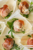 Goat cheese wrapped in bacon. With rocket salad royalty free stock photography