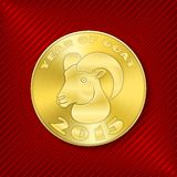 Goat coin. Golden round concentric circle pattern textured metal coin with Chinese New Year 2015 symbol goat design on luxury red striped background Stock Images
