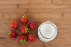 Goat milk yogurt in glass jar and strawberries on a wood background from the top.  Royalty Free Stock Photo