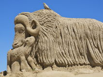 Goat sand sculpture. Sand sculpture of a giant horned goat and calf against blue sky background Royalty Free Stock Photography