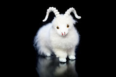 Goat or sheep the symbol 2015 year. White goat or sheep toy the chinese symbol of 2015 year on black background with reflection royalty free stock photography