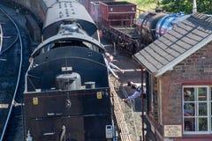Men exchanging rail safety tokens on historic train line. Goathland Yorkshire UK - 25 June 2018: Men exchanging rail safety tokens on historic train line stock photo