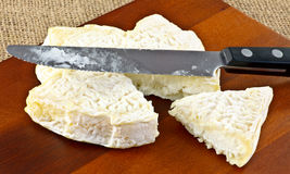 Goat cheese and knife. A closeup of french goats cheese with a slice cut out and a knife royalty free stock image