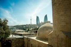 Gobbez of an old mosque in Baku Old city with the new city background. Royalty Free Stock Photos