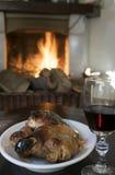 Gobelet de vin rouge et porcelet de rôti dans le thefireside avant Photo libre de droits