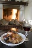 Gobelet de vin rouge et porcelet de rôti dans le thefireside avant Images libres de droits