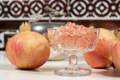 Gobelet en cristal complètement de grains blancs de grenade près de plusieurs fruits Image stock