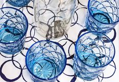 Gobelets en verre bleus avec le décanteur blanc Vaisselle de cuisine de verre bleu photographie stock libre de droits