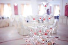 Gobelets en verre Pyramide de champagne Les verres vin et cerises de colline pour l'alcool Boisson de fête Décorations Photos libres de droits