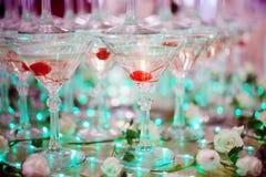 Gobelets en verre Pyramide de champagne Les verres vin et cerises de colline pour l'alcool Boisson de fête Exposition de barman Photo stock