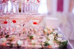 Gobelets en verre Pyramide de champagne Les verres vin et cerises de colline pour l'alcool Boisson de fête Exposition de barman Image stock