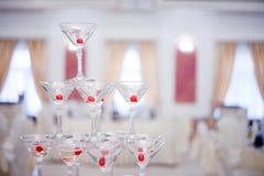 Gobelets en verre Pyramide de champagne Les verres vin et cerises de colline pour l'alcool Boisson de fête Exposition de barman Photographie stock libre de droits