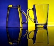 Gobelets en verre sur un fond coloré Photo libre de droits