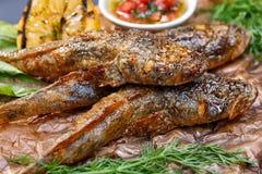 Gobio frito de los pescados con la salsa en un tablero de madera Foto de archivo