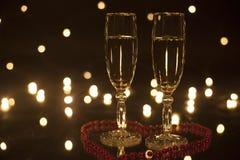 Goblet δύο του άσπρου κρασιού στην καρδιά που ευθυγραμμίζεται με τις χάντρες Αστράψτε φω'τα στο υπόβαθρο Στοκ φωτογραφίες με δικαίωμα ελεύθερης χρήσης