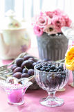 Goblet of blackberries, basket of plums Royalty Free Stock Photography